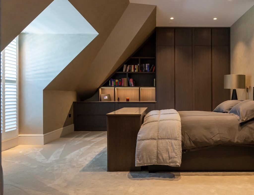 Stained oak fitted cabinet conceals entertainment system at the end of the bed